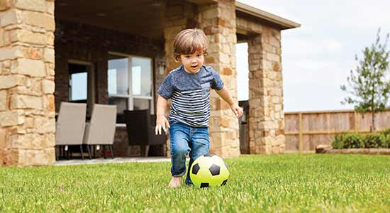 child playing with soccer ball in large yard