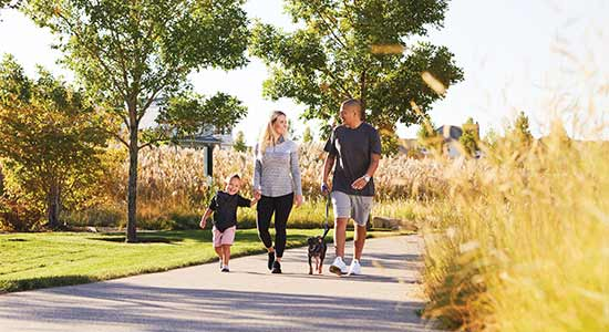 family walking dog on paved trail