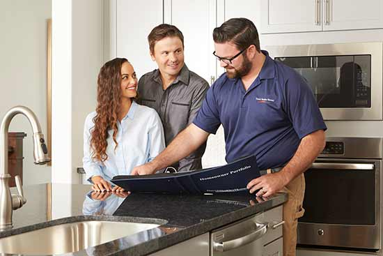 pman and woman in kitchen with man showing them information inside a notebook