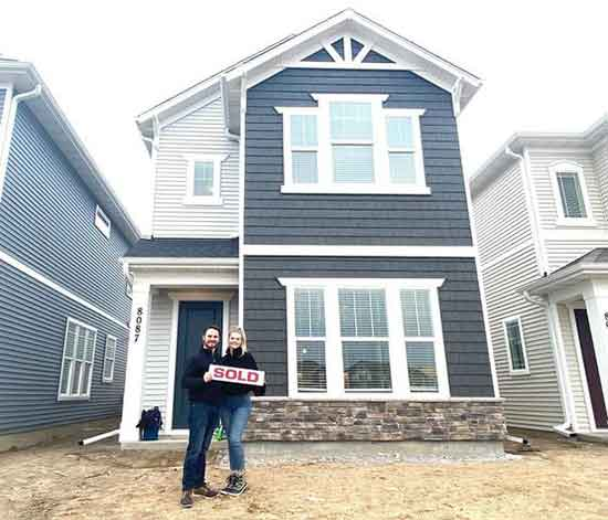 new homeowner couple standing in front of their newly constructed home holding a SOLD sign