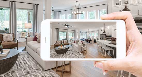 hand holding mobile phone with photo of living room on it
