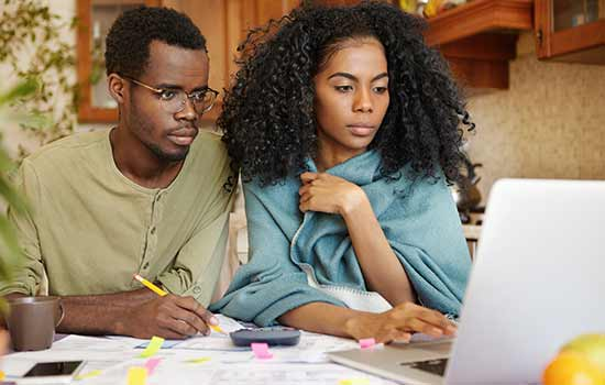 a man and a woman sitting at a table with papers and both are looking at a laptop screen