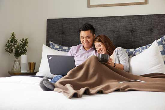 man and woman in bed looking at laptop