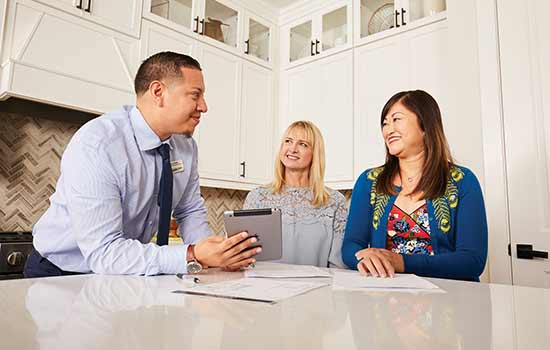 three people standing around kitchen counter smiling at each other