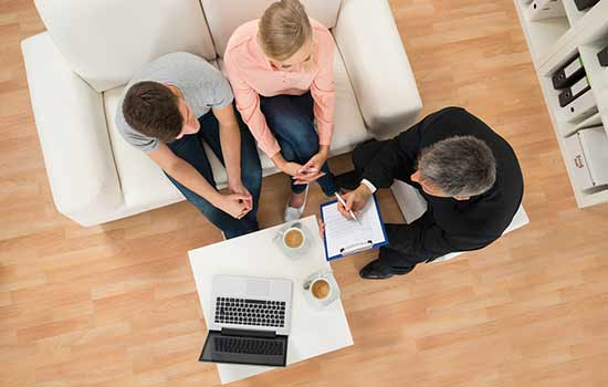 overhead view of three people sitting in chairs looking at a laptop