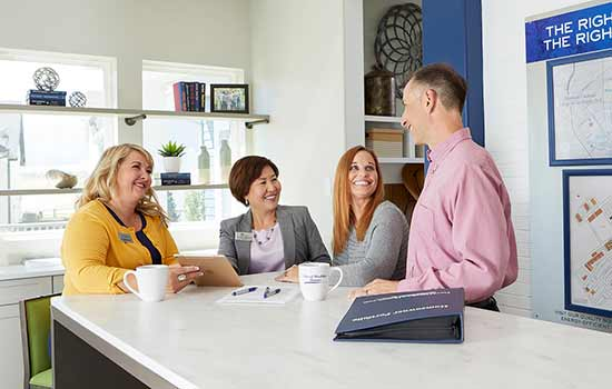 four people sitting a counter and smiling at each other