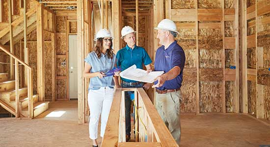 man and woman talking to builder in partially constructed home