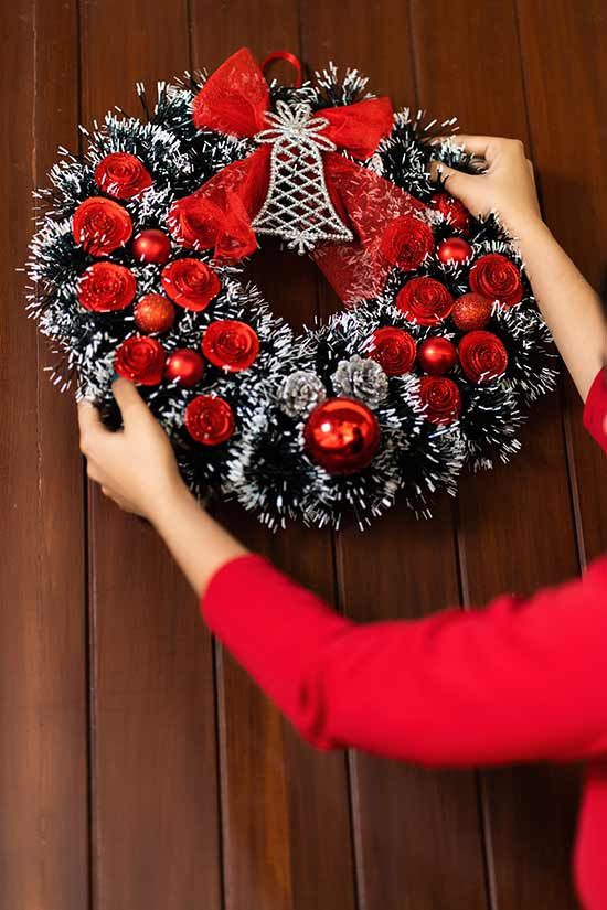 woman hanging up a christmas wreath on a door