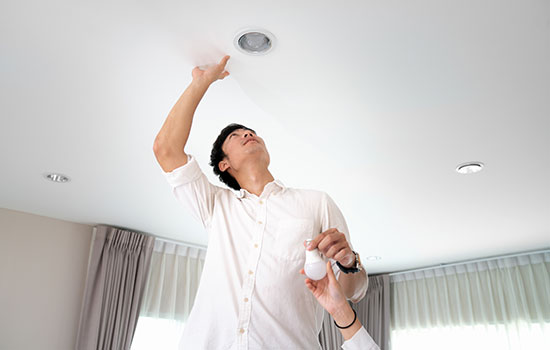 man changing light bulb in ceiling light fixture