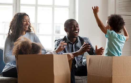 family with smal children playing in moving boxes